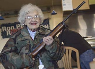 An elderly woman holds a gun, wearing a camouflage jacket.